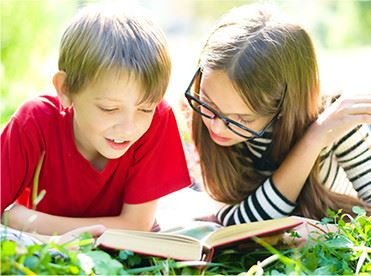 A girl and a boy reading in the grass