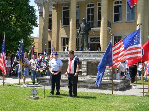 Image of servicemember and resident standing in front on war memorial