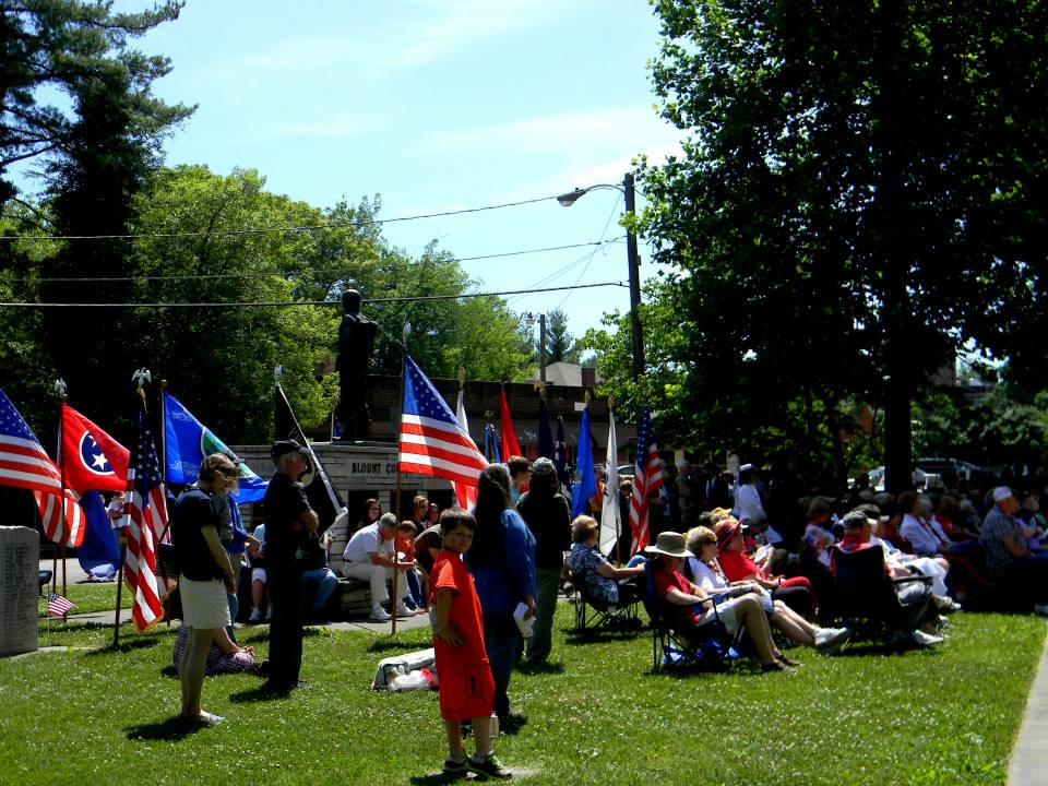 Image of crowd with flags on lawn, some sitting some standing
