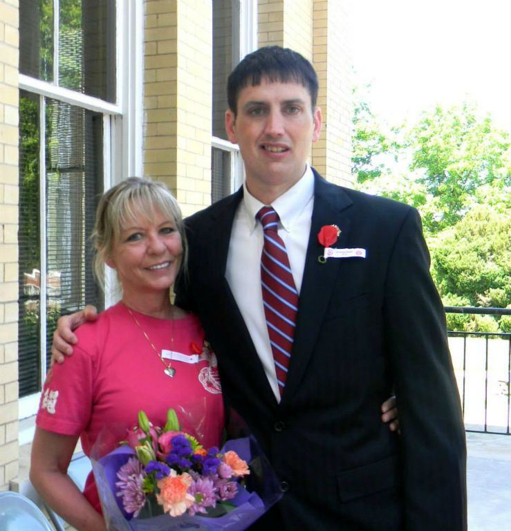 Man in suit and woman in pink, standing and smiling
