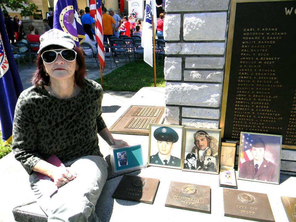 Woman sitting on ledge beside photographs of veterans
