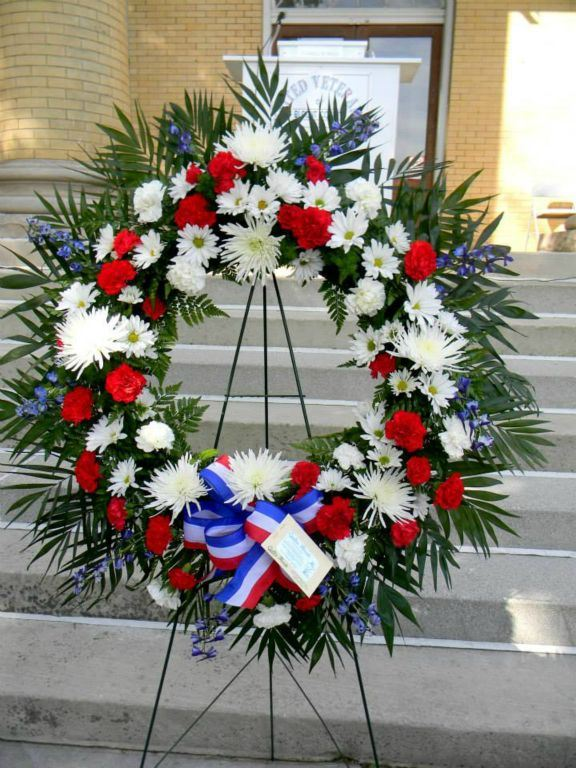 Wreath of red and white flowers, with greenery, and flag ribbon