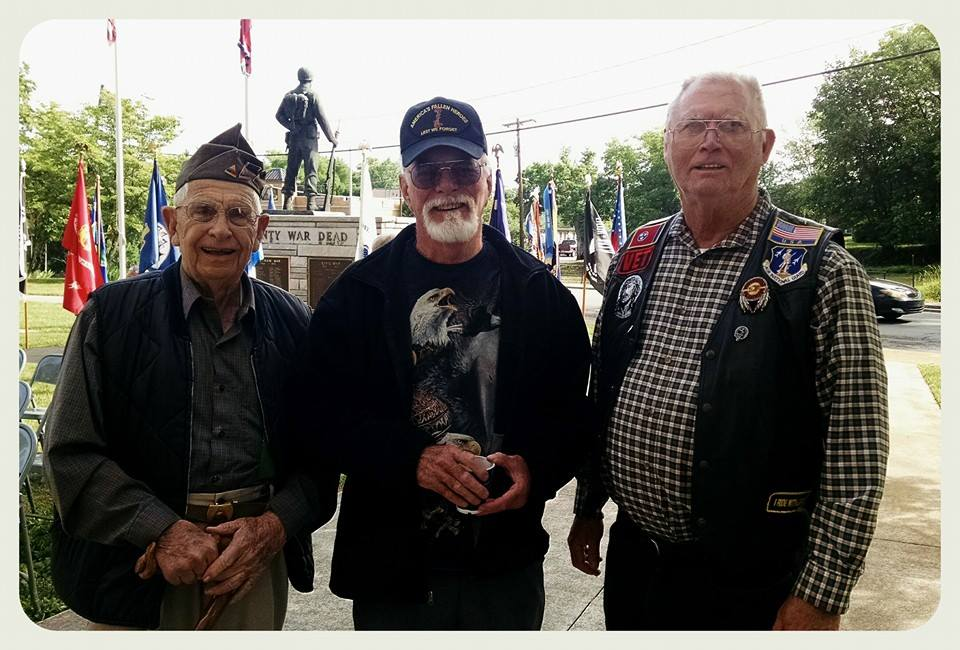 Three men attendees standing together and smiling