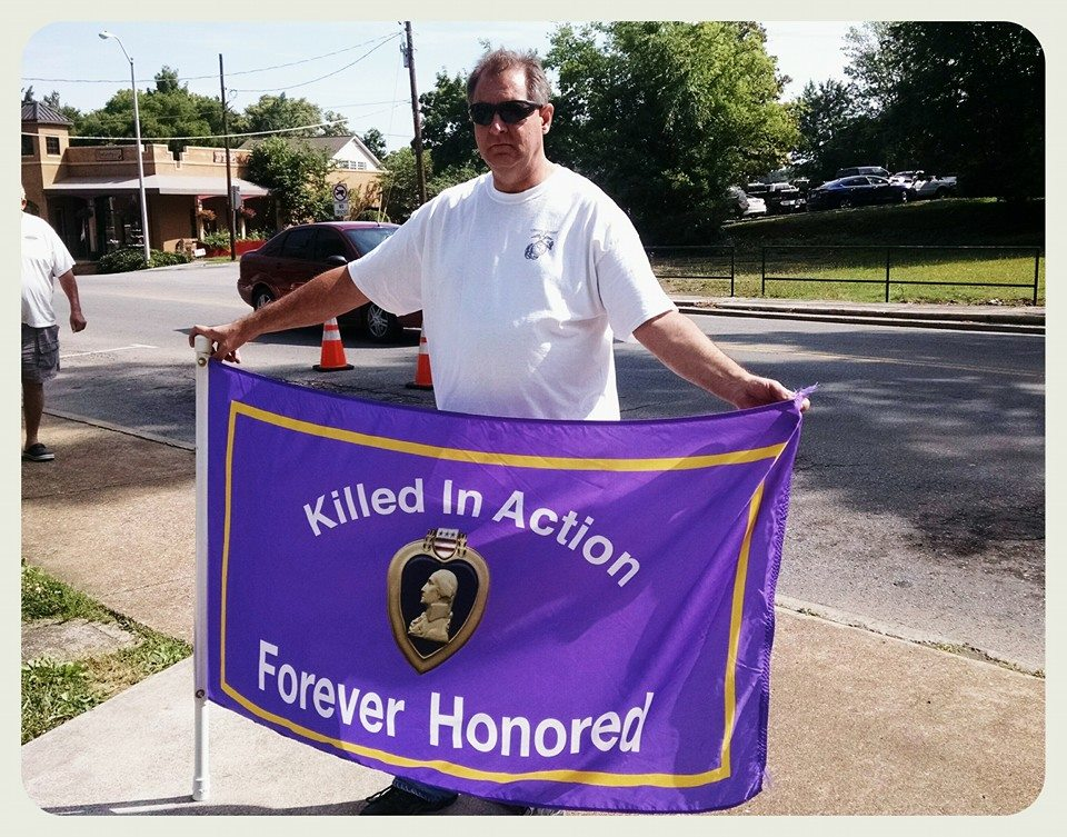 Man holding Purple Heart flag out