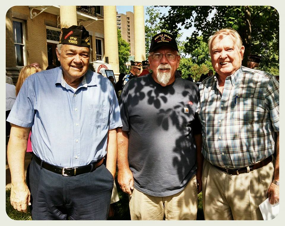 Three men standing in shade smiling