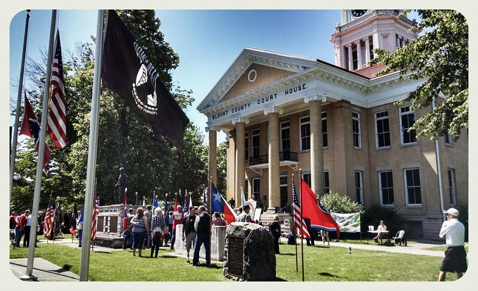 Image of lawn , crowd, flags, and memorial in front of Court House