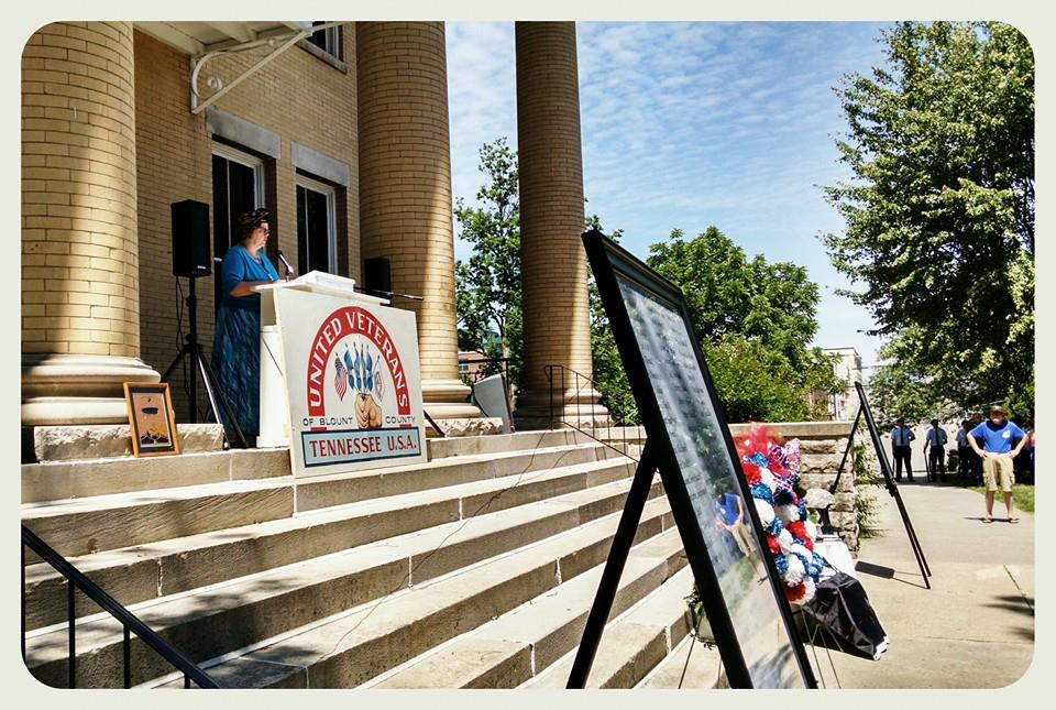 Speaker standing at podium at top of Court House stairs, list of War Dead in view