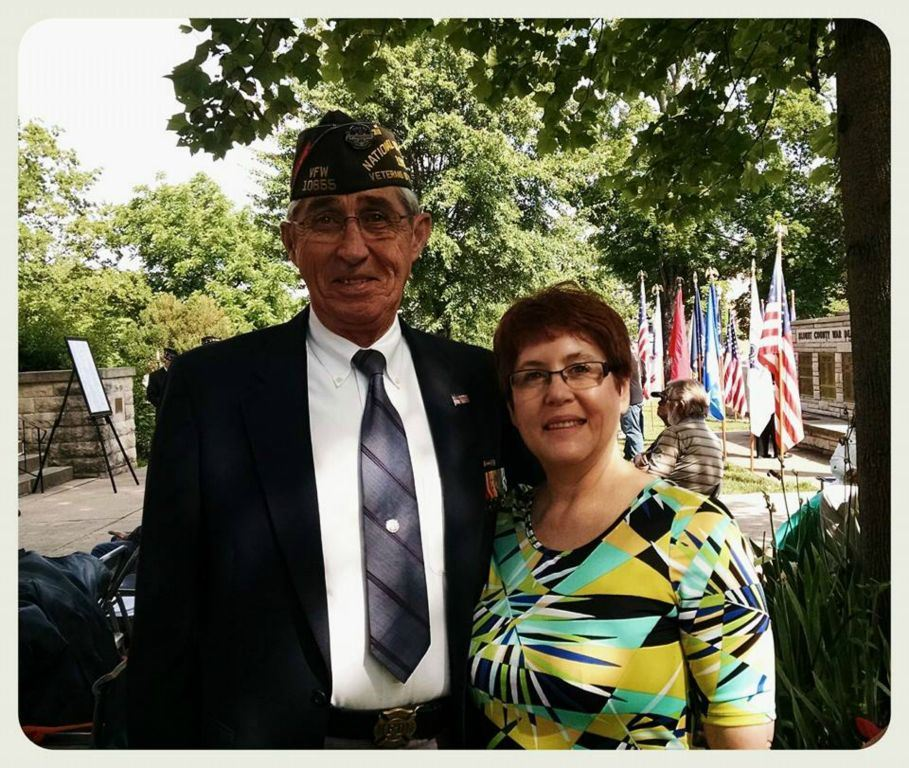 Man veteran and woman standing in shade, smiling