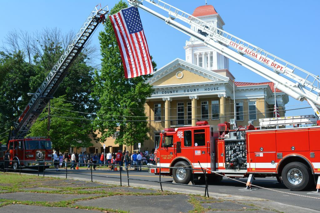 Two firetruck ladders with American flag suspended between them, Court House in background