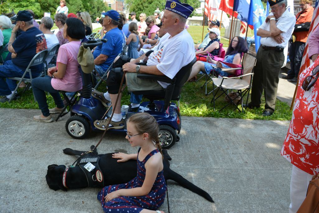 Veteran in motorized scooter with black lab service dog, little girl petting dog