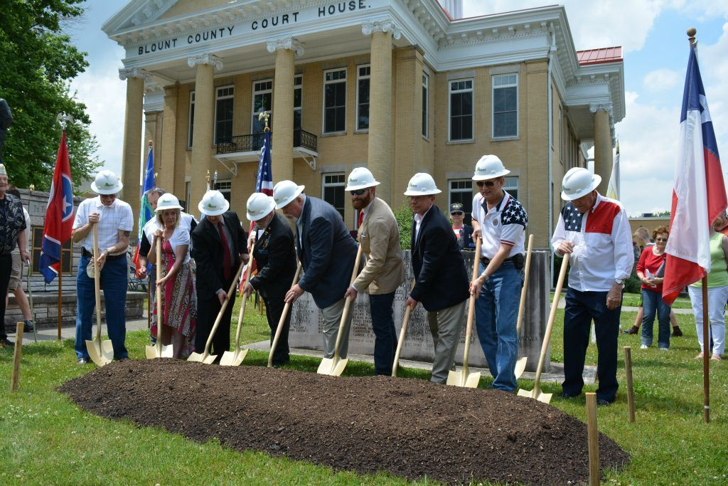 Eight shovelers with hardhats on, with shovels, in front of patch of dirt