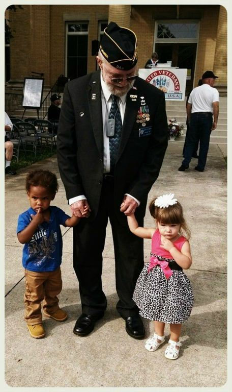 Older veteran holding hands of two small toddlers, one boy and one girl