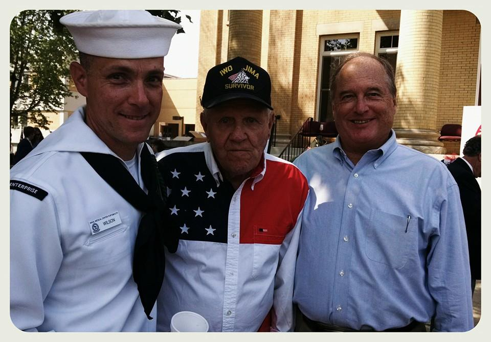 One Navyman, one veteran, and another man standing and smiling