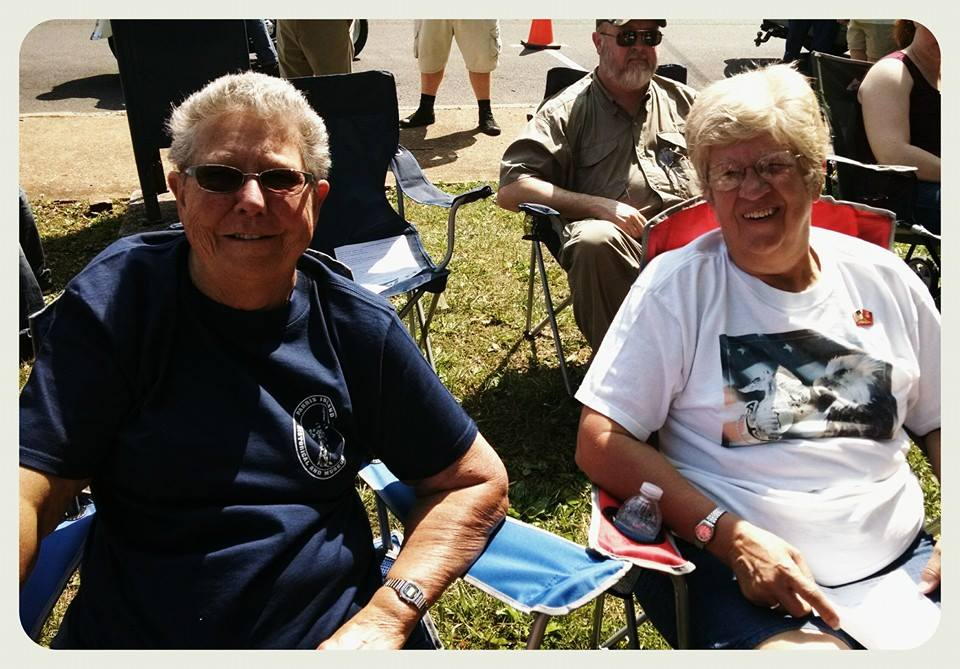 Man and woman sitting beside one another in lawn chairs, in sun