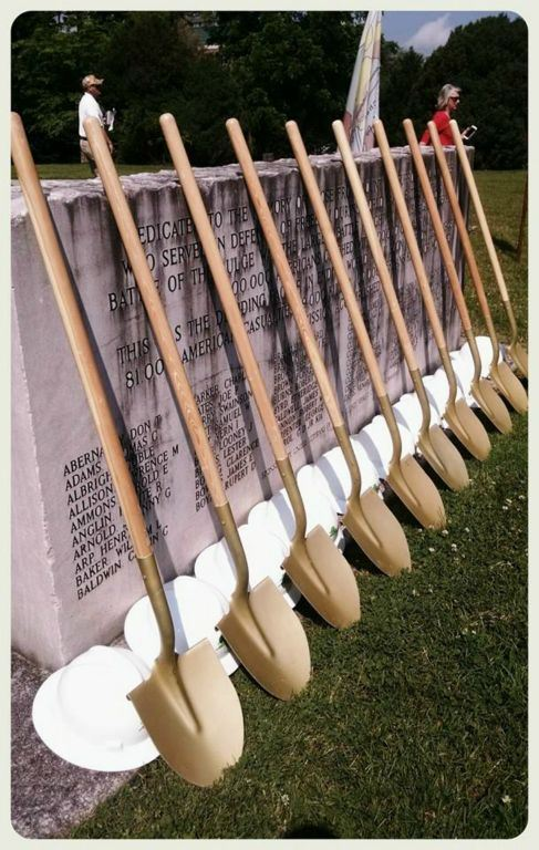 Shovels and hard hats leaned against stone memorial