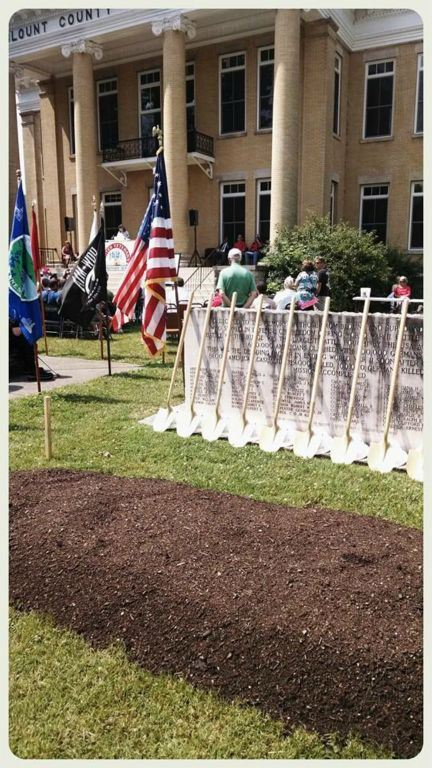 Image of dirt pile, and shovels leaning against memorial