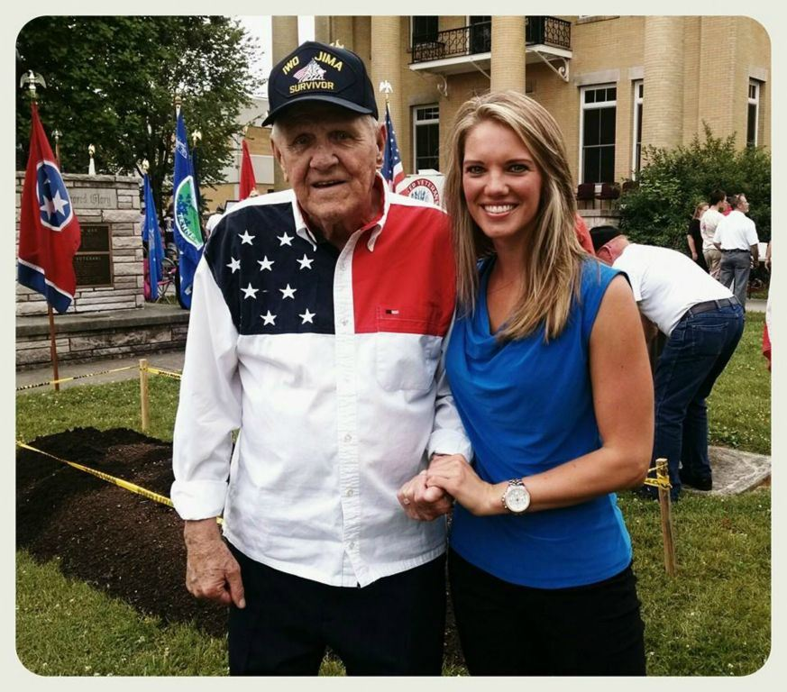 Patriotic veteran with young woman standing and smiling