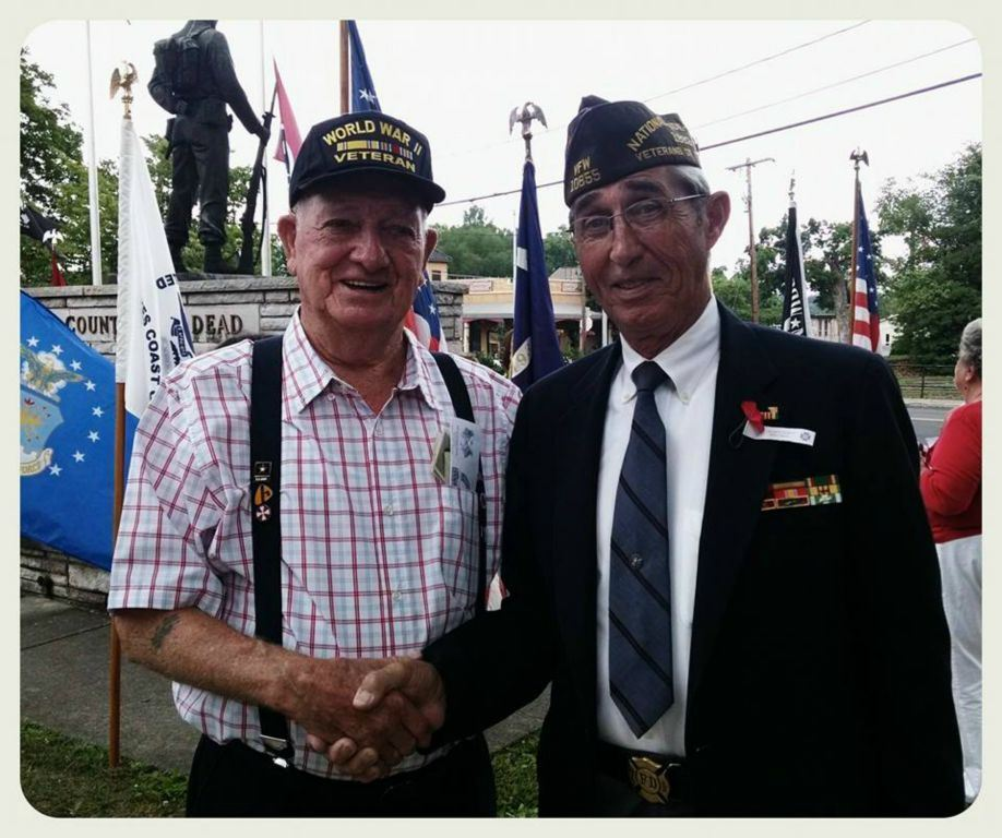 Two veterans, one in uniform, shaking hands