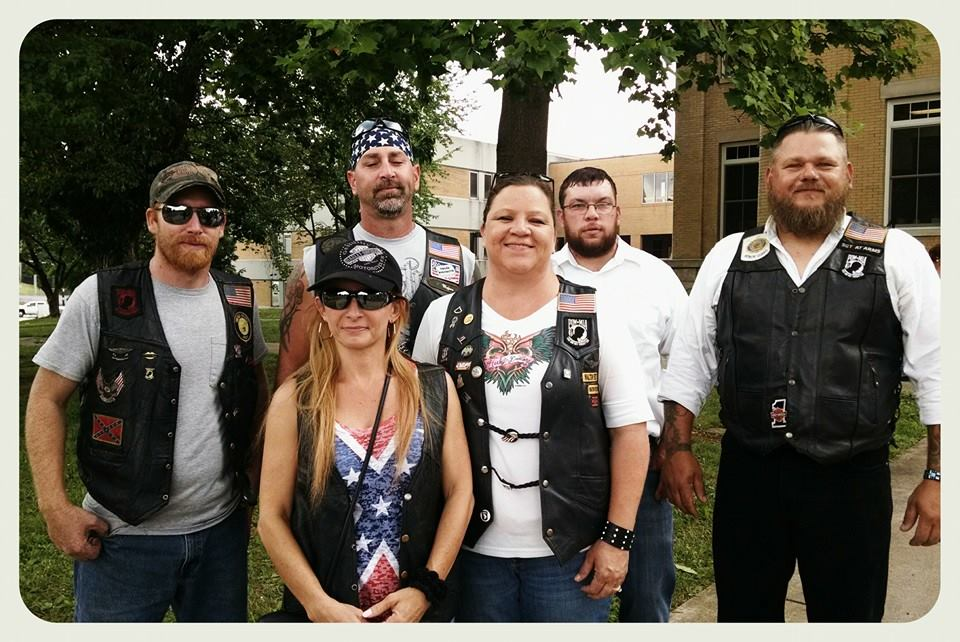 Seven attendees in biker gear, standing and smiling
