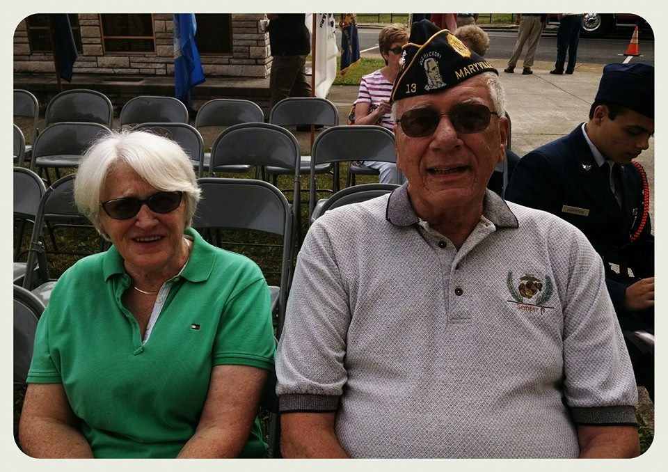 Woman in green shirt beside man with veteran hat one, sitting