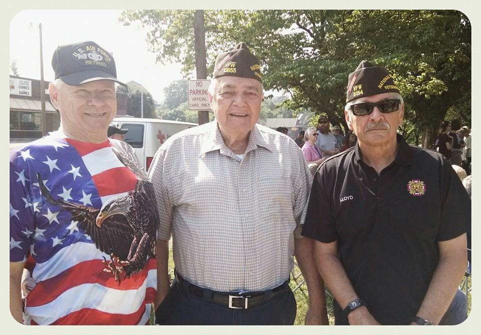 Three veterans standing and smiling together