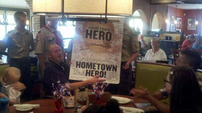 "Group of people surround man with sign ""hometown hero"""