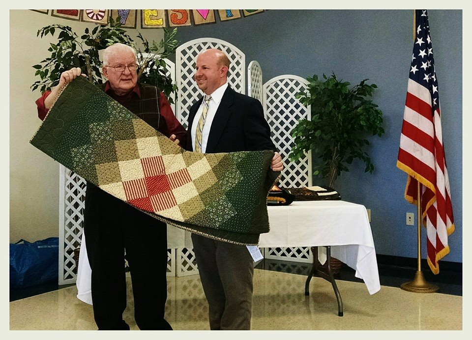 Man presenting veteran with green, red, and cream colored quilt
