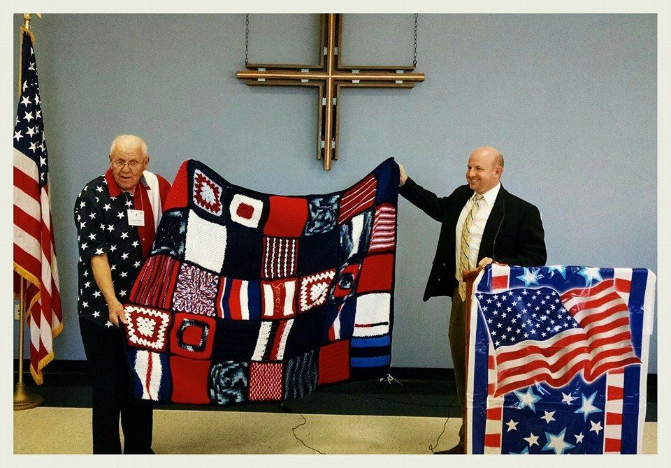 Two men holding up ta nautical flag blanket