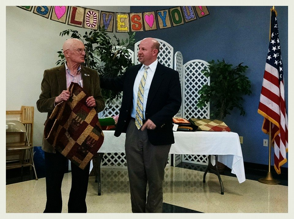 Man gifting a veteran a brown and red quilt