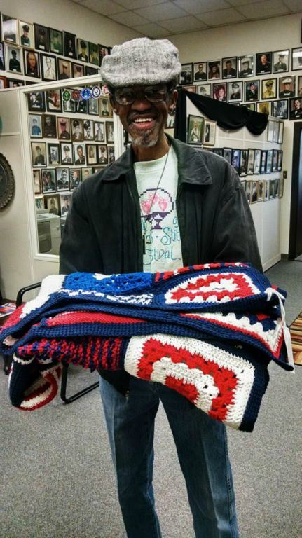 Standing man, wearing hat, holding red, white, and blue blanket in hands