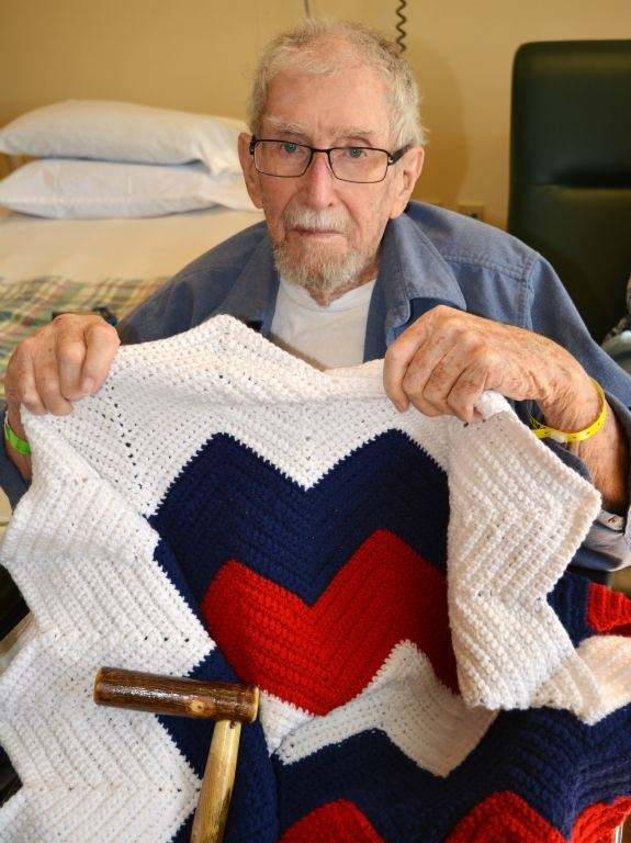 Veteran, with glasses, holding up a red, white and blue knitted blanket