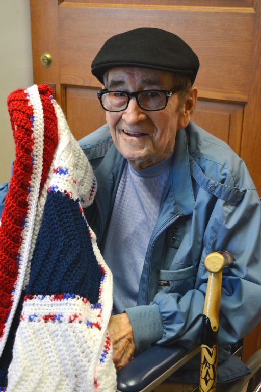 Veteran, with glasses and wearign a hat, holding up a red, white and blue knitted blanket