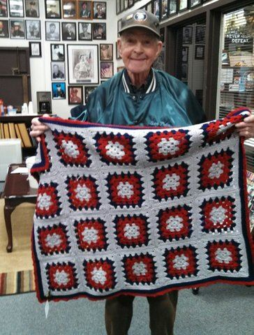 veteran displaying red, white, and blue quilt
