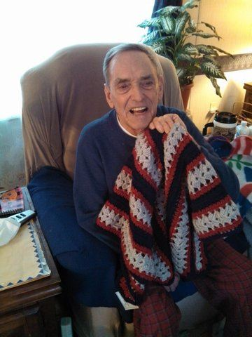 Man sitting in chair, smiling and holding quilt