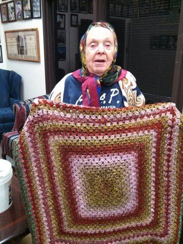 Standing woman holding up a pink, brown, and red quilt