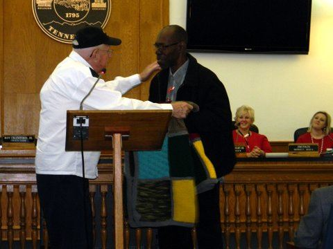 Man presenting quilt to veteran, standing at podium