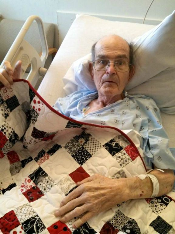 Man with glasses, in hospital bed with quilt