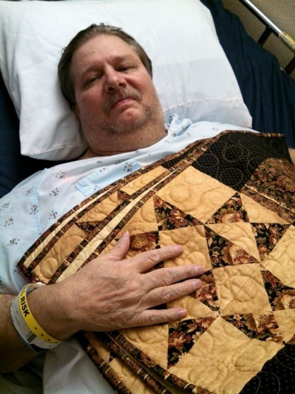 Man in hospital bed with yellow quilt