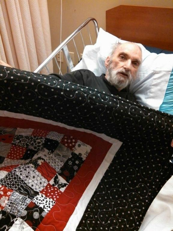 Veteran in hospital bed holding up quilted blanket