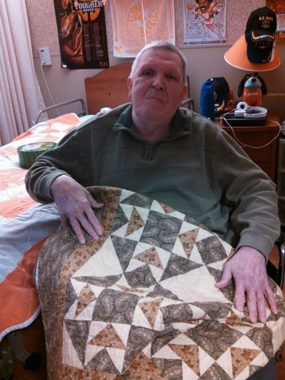 Man in green shirt, sitting with quilt on his lap