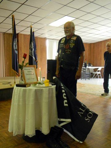 Man standing beside the POW-MIA table and chair