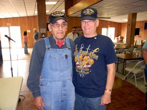 Man in overalls standing beside man in blue shirt, both are smiling
