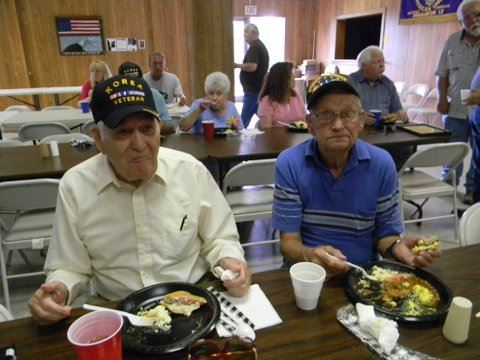 Two veterans enjoying a meal, sitting at a table