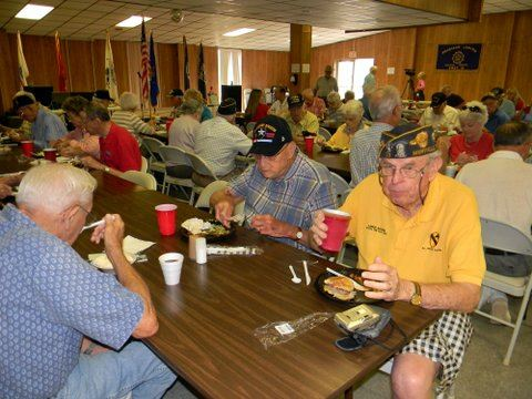 Group picture of veterans and attendees eating