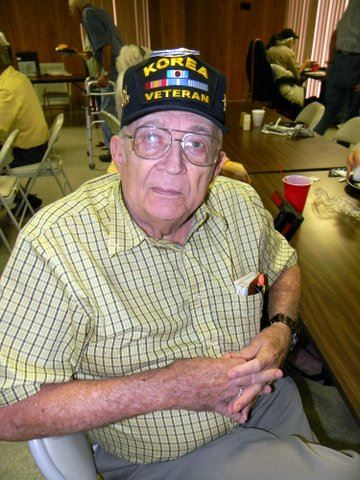 Man sitting, with hands folded, wearing a checked shirt and Korean War veteran hat