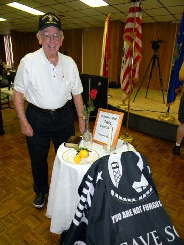 Man in white shirt, standing and smiling at the POW-MIA table and chair