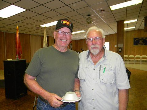 Two veterans standing beside each other, one with bowl in hand, both smiling