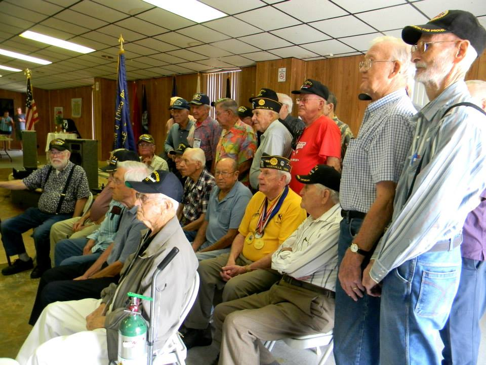 Image of all the attending veterans, sitting and standing together, from side