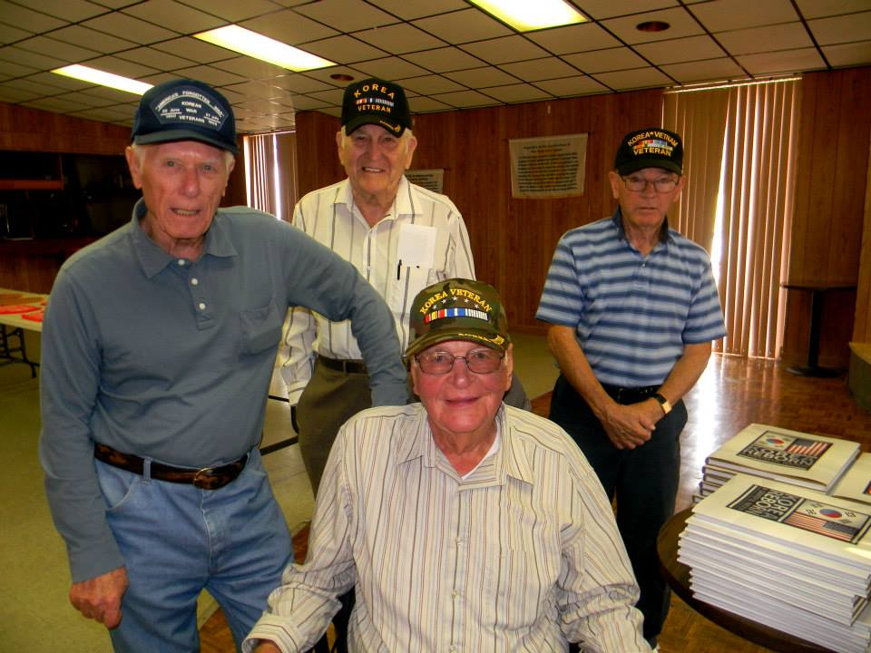 Groups of four veterans, one sitting the others standing, all wearing Korean War veteran hats and smiling