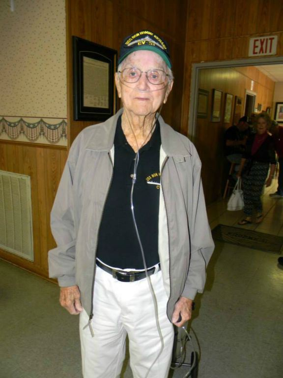 Man in black shirt with jacket and Korean War veteran hat, standing and smiling